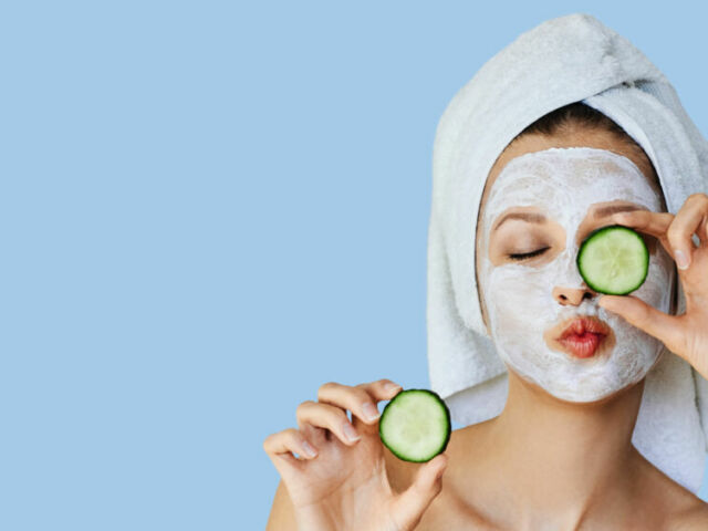 Beautiful young woman with facial mask on her face holding slices of cucumber. Skin care and treatment, spa, natural beauty and cosmetology concept.